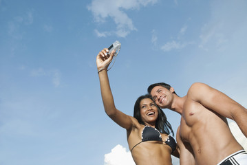 Couple in bathing suits taking self-portrait with digital camera