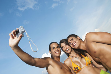 Friends in bathing suits taking self-portrait with digital camera