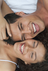 Laughing Hispanic couple laying together