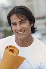 Hispanic man holding yoga mat