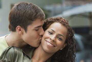 Boyfriend kissing smiling girlfriend