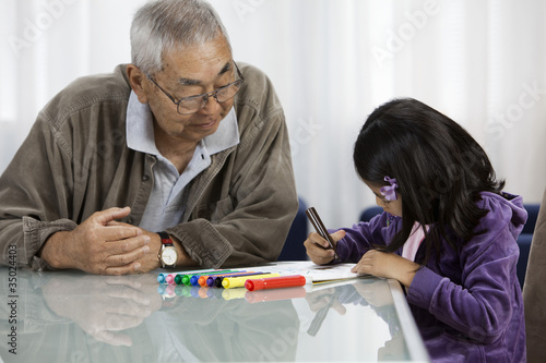 Asian grandfather watching granddaughter drawing