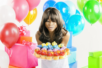 African American woman with birthday presents and cupcakes