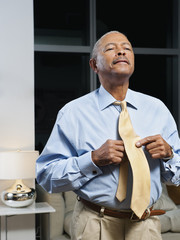 Black man adjusting tie