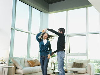 Couple dancing together in living room