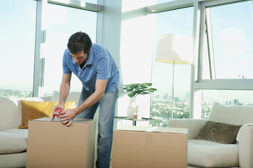 Caucasian man taping cardboard box in living room
