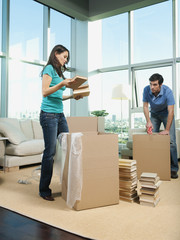 Couple packing boxes in living room