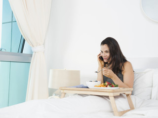 Mixed race woman eating breakfast in bed