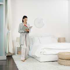 Mixed race woman reading book in bedroom