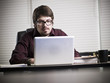 Serious Hispanic businessman working on laptop