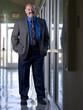 Hispanic businessman standing in office corridor