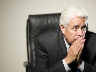 Uncertain Hispanic businessman sitting in chair
