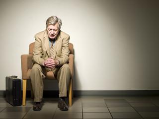 Sad Caucasian businessman sitting in chair