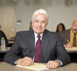 Hispanic businessman writing in notepad
