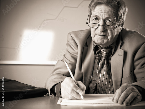 Sad Caucasian businessman writing at desk