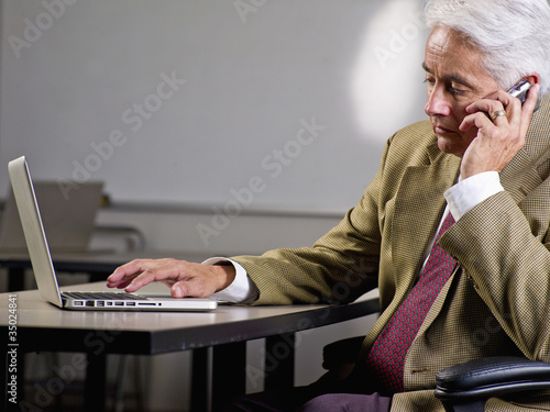 Hispanic businessman using laptop and talking on cell phone