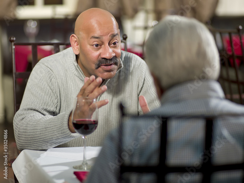 Hispanic men having dinner together in restaurant