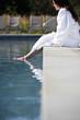 Woman soaking feet in swimming pool