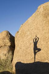Shadow of Hispanic woman practicing yoga on rock