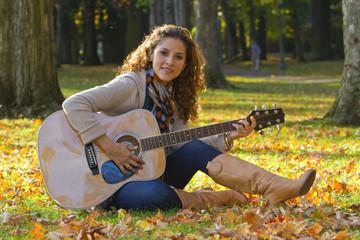 Hispanic woman playing guitar in park