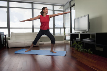Hispanic woman exercising on yoga mat