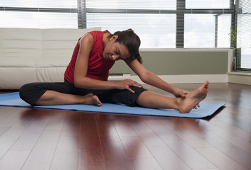 Hispanic woman stretching on yoga mat