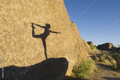 Shadow of Hispanic woman practicing yoga on rock