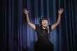 Elegant Asian woman singing into microphone with arms raised