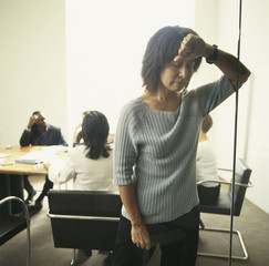 Businesswoman leaning wall with co-workers in background