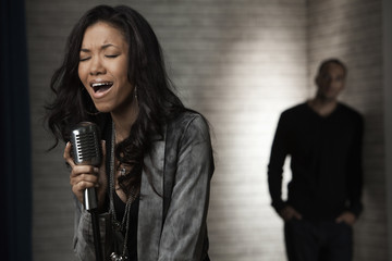 Man watching African American woman singing into microphone