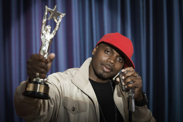 Black man holding trophy speaking at microphone