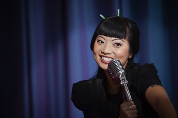 Elegant Asian woman singing into microphone