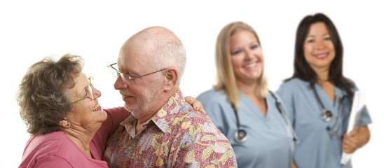Affectionate Senior Couple with Medical Doctors or Nurses Behind