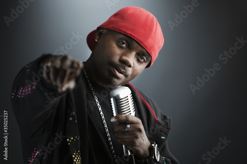 Serious Black man holding microphone and pointing