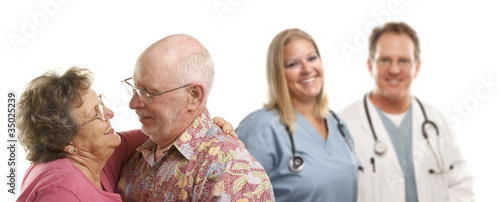 Sweet Senior Couple with Medical Doctors or Nurses Behind