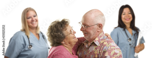 Amorous Senior Couple with Medical Doctors or Nurses Behind