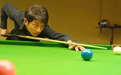 Young man concentrating while aiming at pool ball while playing