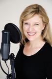 ältere frau spricht in ein mikrophon, lacht, moderatorin