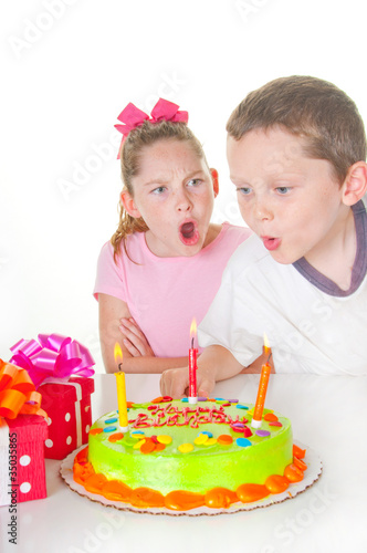 Boy blowing out girl's birthday candles