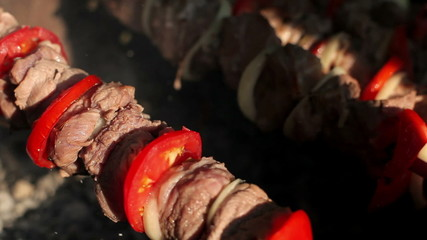 Man prepares pork shashlik on skewers