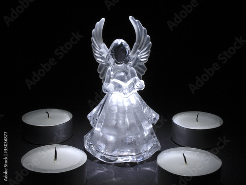 four extinct tea lights surround an angel
