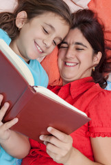 Latin mother and daughter reading in bed