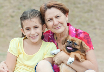 Adorable latin girl, her grandmother and the family dog