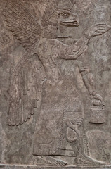Ancient assyrian clay relief depicting an eagle-faced god