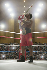 African American kissing trophy in boxing ring