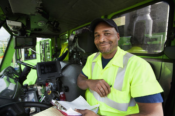 African American man driving garbage truck