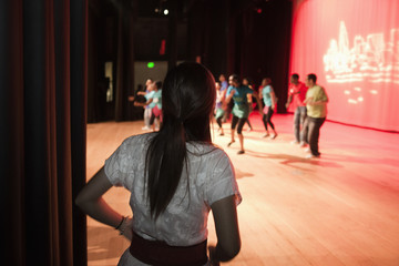 Girl watching teenagers rehearsing on stage