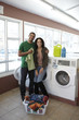 Mixed race couple folding clothes in laundromat
