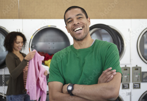 Mixed race man laughing in laundromat