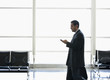 Hispanic businessman text messaging on cell phone in airport